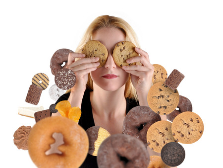 sweet food: A woman has sweet food snacks around her on a white background and she is hiding with cookies on her eyes. Stock Photo
