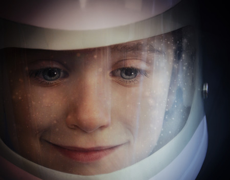 A young boy is wearing an astronaut helmet and looking into space with stars for an education or imagination concept.