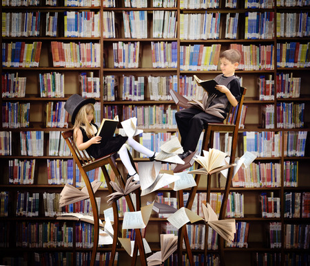 books: Two children are reading books on long, surreal wooden chairs in a library with books and papers flying around them for an education or imagination concept.