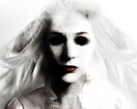 A scary evil woman with black eyes and red lips is death on a white background for a fear or Halloween concept.