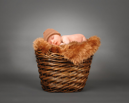 A cute little baby is sleeping in a wooden basket with brown fur and is wearing a hat. The baby could be a boy or girl on a isolated gray photography backdrop for a parenting or love concept. Stockfoto
