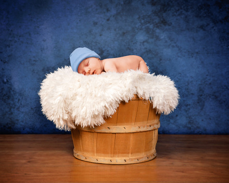 A newborn baby is sleeping in a wooden basket with white fur and is wearing a hat on a blue background. The baby is sleeping. Use for a photography portrait or parenting concept. Standard-Bild