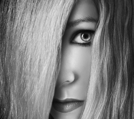 A girl is hiding behind her straight hair in her face in a\ black and white photo. Her eye is peaking out and she is serious\ for a beauty or secret concept.