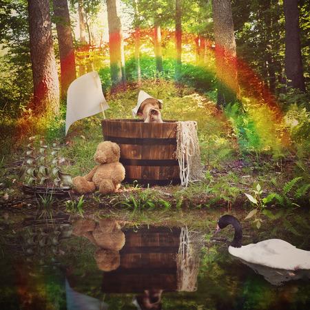 若い男の子は、想像力の白鳥が付いている水で魚や旅行の概念をふりをして森の中で木製の樽に座っています。