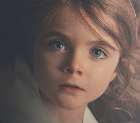 A young little child is looking into the camera with a serious expression. The closeup of the girl shows her hair and blue eyes for a beauty or innocence concept. photo