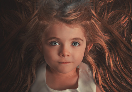 timeless: A closeup of a beautiful little girl is laying down with her hair out for a salon hairstyle or innocence concept.