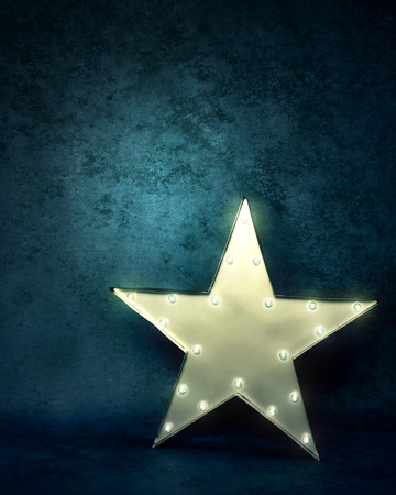 A bright glowing star light is standing on a  textured blue background with text area to add your message. photo