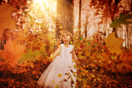 A little girl is in the woods with trees and fall leaves blowing in the wind around her. The child is wearing a white pretty dress for a season or happiness concept.