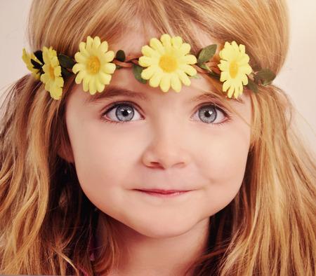 Een close-up van een gelukkig meisje draagt een gele bloem krans op haar haar voor een schoonheidsbehandeling of lente-concept.