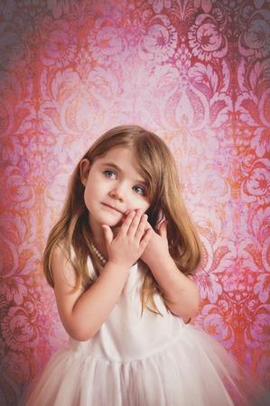 Een mooi klein meisje draagt een witte prinses jurk met een roze damast achtergrond voor een schoonheid of speeltijd concept.