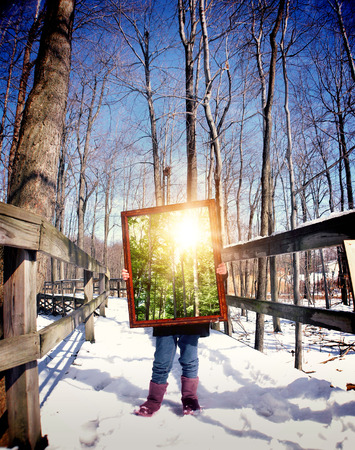 A child is standing on a winter trail in the woods holding a wooden frame with a picture of the summer with sunshine for a season concept.