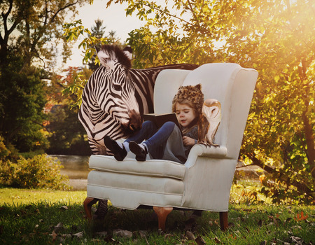 A young child is reading a book on a white chair with a zebra and owl next to her in nature for an education or creativity concept.