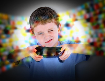 A young boy is playing a video game with a controller. He is concentrating hard for a entertainment or leisure concept.