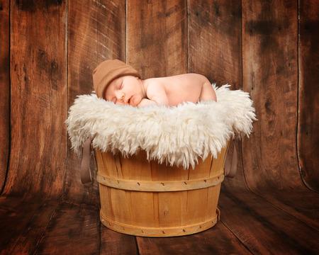 nato: A cute neonato dorme in un cestino di legno con uno sfondo in legno e indossa un cappello per una fotografia ritratto o concetto di amore. Archivio Fotografico