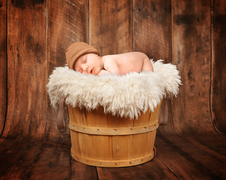 new born baby girl: A cute newborn baby is sleeping in a wooden basket with a wooden background and is wearing a hat for a photography portrait or love concept.