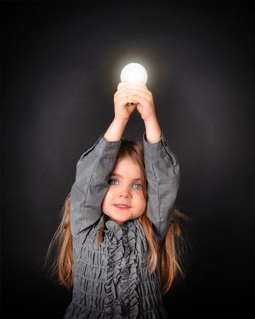 작은 아이 교육 또는 교육 개념에 대한 격리 된 검정색 배경에 밝은 빛나는 전구를 잡고있다. 스톡 콘텐츠