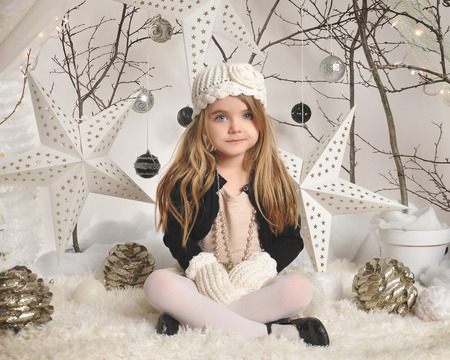 A little girl is sitting in a white winter wonderland setup with trees, hanging stars and Christmas lights in the background for a season or holiday concept. 免版税图像