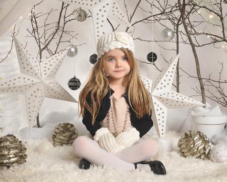Holčička sedí v bílé zimě nastavení divů stromy, závěsné hvězdy a vánoční světla v pozadí pro sezonu nebo sváteční koncepce a.