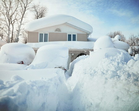 A house, roof and cars are covered with deep white snow in western new york for a weather or blizzard concept. Stockfoto