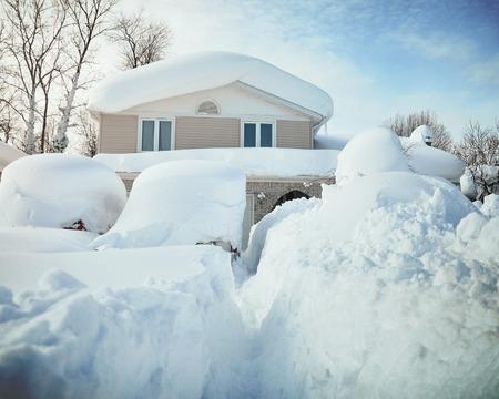 Ein Haus, Dach und Autos sind mit tiefen weißen Schnee in den westlichen New York für ein Wetter oder Schneesturm Begriff fallen.