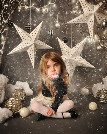 A little child is sitting on a winter wonderland backdrop with trees and white stars. She is blowing snow in her hand for a season or holiday concept.