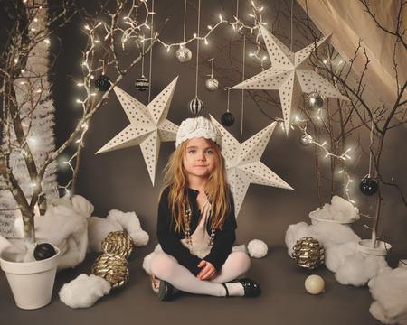 어린 소녀는 계절이나 휴일 개념에 대한 배경 주위에 별과 크리스마스 장식을 매달려, 나무와 겨울 원더 랜드 SetIP 프로그램에 앉아있다.