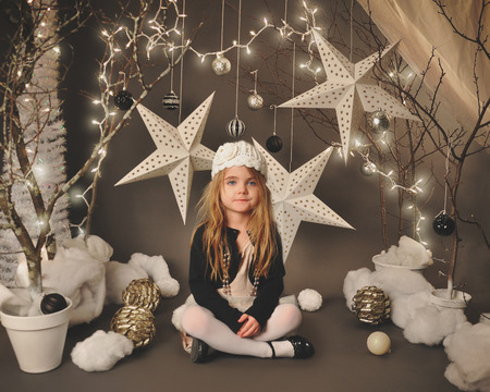 portrait studio: A little girl is sitting in a winter wonderland setip with trees, hanging stars and christmas lights around the background for a season or holiday concept. Stock Photo