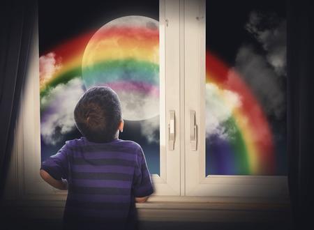 어린 소년 상상력이나 창의적인 개념에 대 한 무지개와 함께 큰 달 밤에 창에서 찾고 있습니다. 스톡 콘텐츠