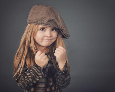 모자와 함께 작은 복고 소녀는 그녀의 주먹을하고 안전 또는 강도 개념에 대 한 회색 배경에 강력 하 고 힘든 것 같습니다.