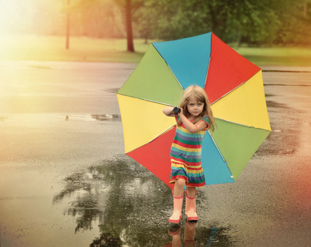 A little girl is walking with a rainbow umbrella in her hand and rubber boots outside at a park for a weather or season concept.