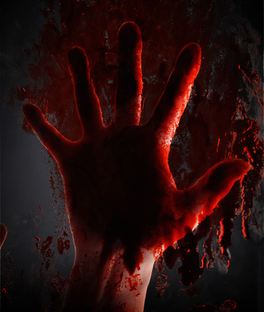 A scary bloody hand is smearing red blood on a window on a black background for a horror or killer concept.