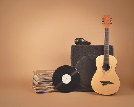 오래 된 비닐 레코드 및 앰프와 어쿠스틱 나무 기타 스택 음악 또는 밴드 개념에 대 한 갈색 배경에 격리됩니다.
