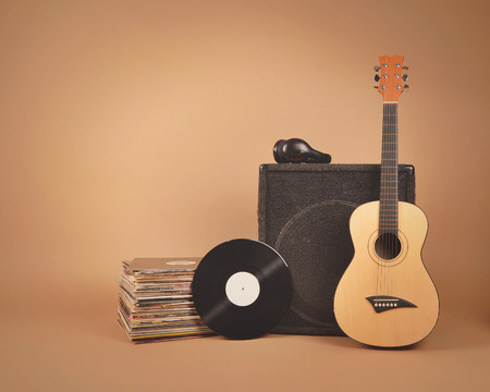 A stack of old vinyl records and acoustic wooden guitar with an amplifier are isolated on a brown background for a music or band concept. Archivio Fotografico