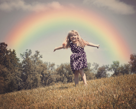 rainbow scene: A little child is dancing in an open grass field with wind blowing in her hair and a rainbow in the background for a freedom or spring concept. Stock Photo