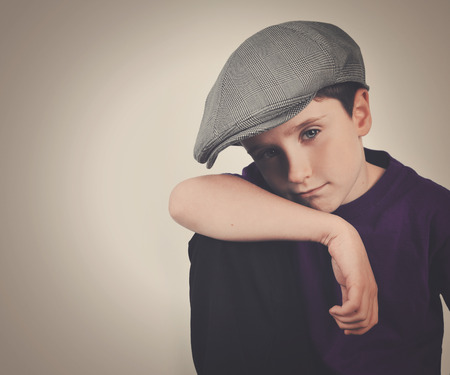 photgraphy: A young retro boy is wearing a driving cap hat and posing with his hand on his knee. There is an isolatd background to add youu message.
