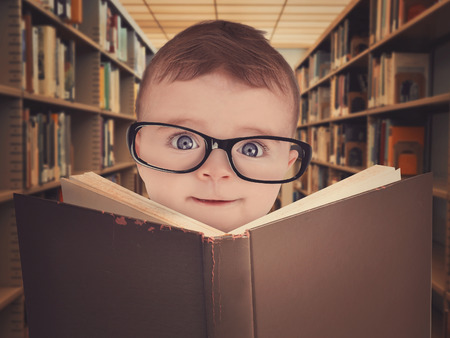 A cute little baby is wearing eye glasses and reading a library book for an education or learning concept.