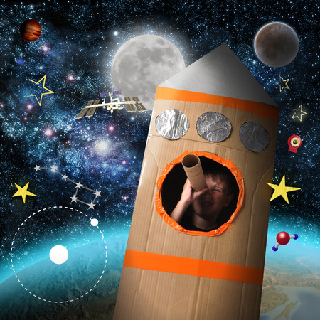A young boy is in a cardboard space rocket ship pretending to be an astronaut and looking at stars with astronomy icons around him.