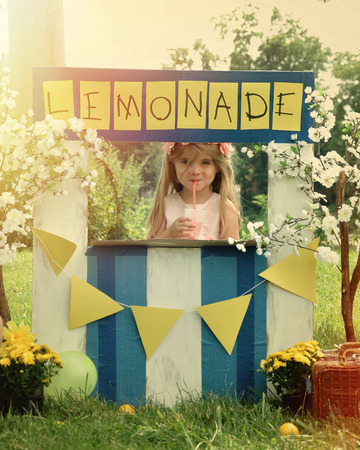 A little girl has an outdoor homemade lemonade stand with a sign and she looks happy for a small business or money concept. Фото со стока