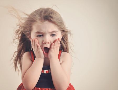 exitacion: Una niña tiene una boca abierta con el pelo soplando sobre un fondo retro para un concepto sorpresa o shock. Foto de archivo
