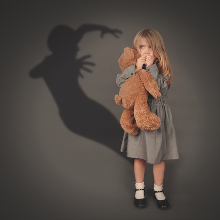 A little girl is holding a teddy bear and looking at a scary dark silhouette of an evil ghost popping out on a gray background.