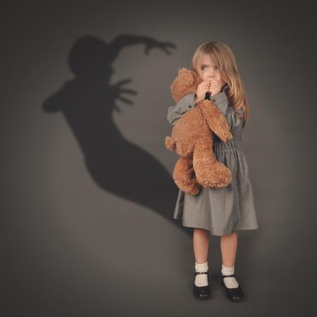 Una niña es la celebración de un oso de peluche y mirando una silueta oscura de miedo de un fantasma maligno saltando sobre un fondo gris.