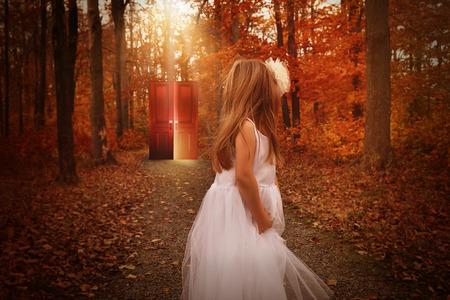 小さな子供が謎や想像力の概念のための木製の道に彼女の後ろに輝く赤いドアを見ると白いドレスを着て、森の中で。
