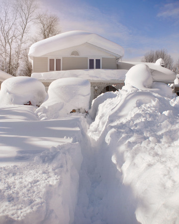 A house, roof and cars are covered with deep white snow in western new york for a weather or blizzard concept. Standard-Bild