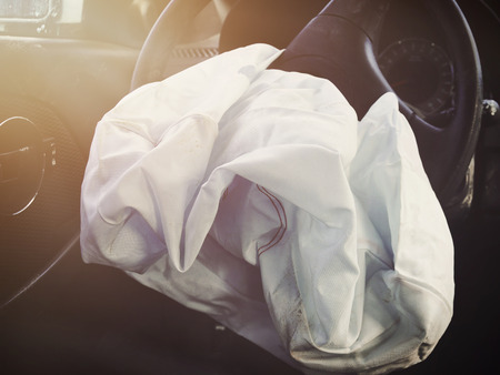 A front car airbag has deflated in a sterring wheel from an accident. Ue it for a safetly or insurance concept. Stockfoto