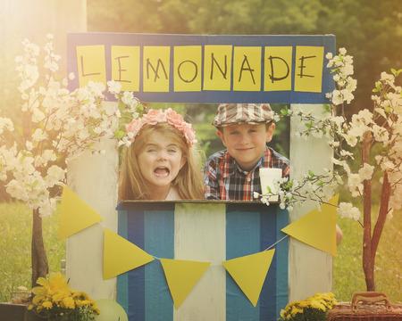두 명의 작은 아이는 기업가 개념에 대 한 서명과 함께 화창한 날에 만든 레모네이드 스탠드에서 레모네이드를 판매하고 있습니다. 스톡 콘텐츠