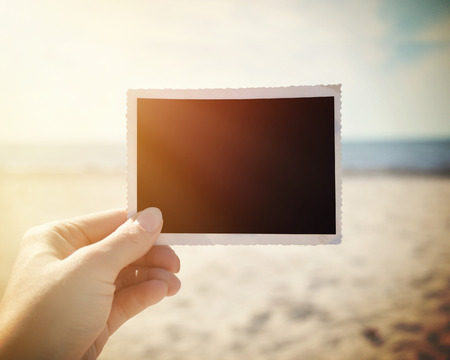 snapshot: A hand is holding up a blank photo snapshot at a sunny beach to add your own photo or message in the area.