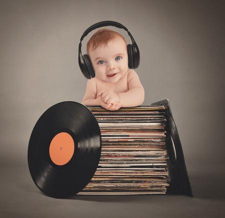 Um bebê está usando fones de ouvido de música com registros de vinil retro em um fundo cinzento isolado por um conceito de parte ou de entretenimento.