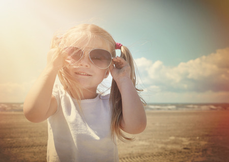 A little retro girl in pigtails is wearing sunglasses at a sandy beach with warm sun shine on her face for a vacation or season concept.