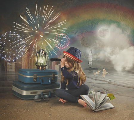 A little girl at the beach is looking through a magnifying telescope at fireworks in the sky with a map and rainbow in the background for a travel imagination concept.