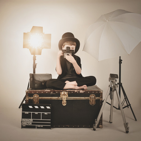 directors: A retro child is holding a vintage camera and focusing with various photography lighting equipment for a director or film concept. Stock Photo